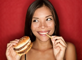 woman-eating-burger-and-fries